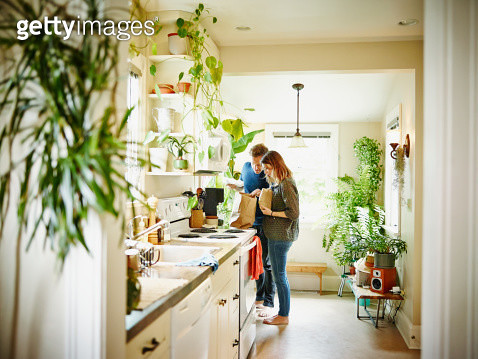 Couple unpacking groceries in kitchen of home - gettyimageskorea