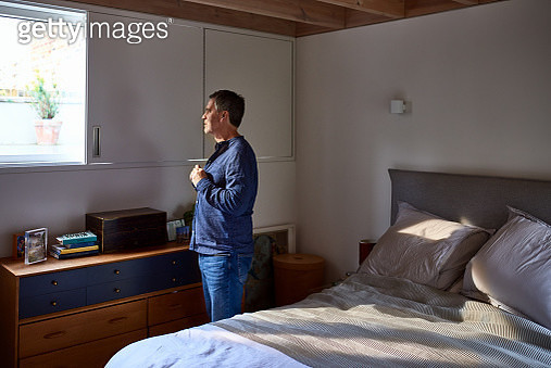 Mature man getting ready in bedroom - gettyimageskorea