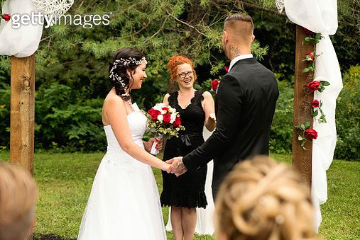 Millennial couple with kids and tattoos saying yes in an intimate outdoors traditional wedding. Here the couple holding hands during the ceremony with woman celebrant. Horizontal full length outdoors shot with some copy space. - gettyimageskorea