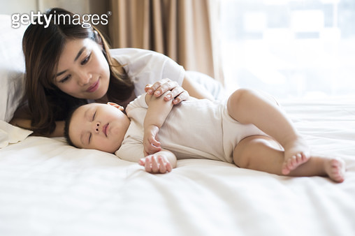 Young Chinese mother with sleeping baby boy - gettyimageskorea