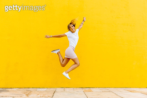 Full Length Of Happy Woman Jumping Against Yellow Wall - gettyimageskorea