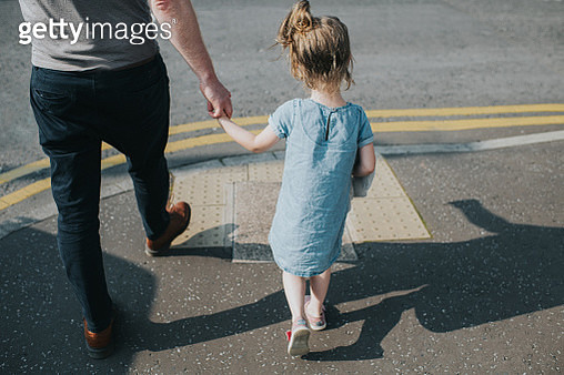 Little girl holding her Father's hand, about to cross a Road - gettyimageskorea