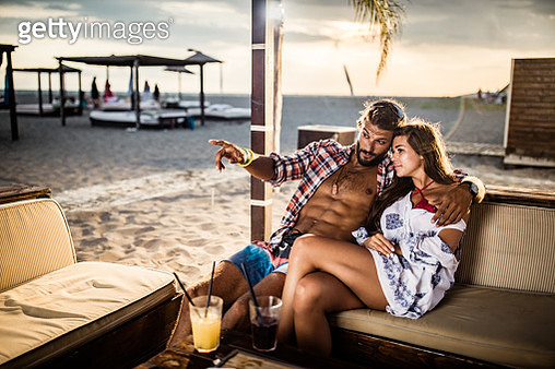 Happy affectionate couple relaxing in a bar at the beach. - gettyimageskorea