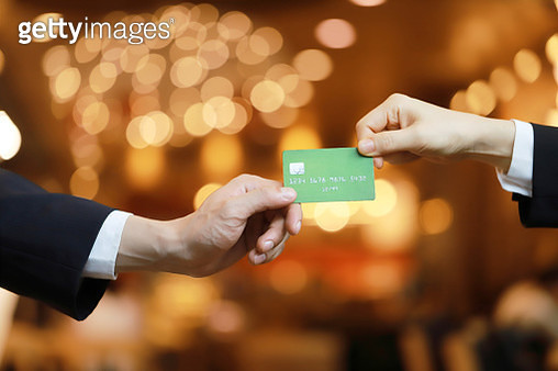 Close-up of two hands with credit card - gettyimageskorea