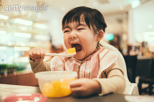 Toddler girl having chopped orange in a restaurant - gettyimageskorea