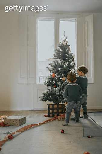 Family decorating Christmas tree - gettyimageskorea