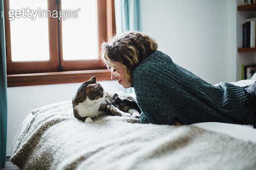 Beautiful young woman with her cat on a bed - gettyimageskorea