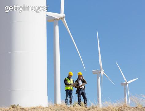 Workers talking by wind turbines in rural landscape - gettyimageskorea