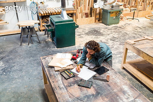 Designer working at a bench in a furniture factory - gettyimageskorea