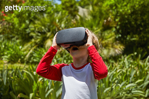 Boy outside in the garden at home using virtual reality headset - gettyimageskorea