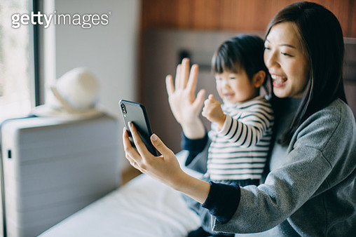 Young Asian mother and cute little daughter having video call on smartphone with family in hotel room while on vacation and smiling joyfully - gettyimageskorea