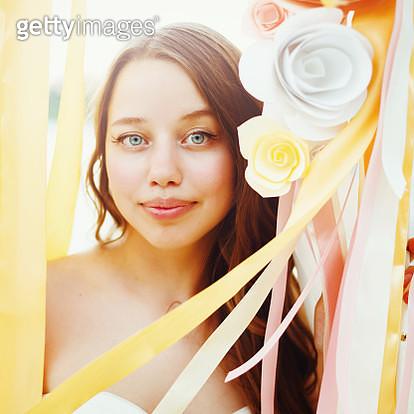 Beautiful bride among paper flowers decoration - gettyimageskorea