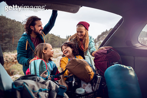 Young family getting the camping supplies out of the car - gettyimageskorea