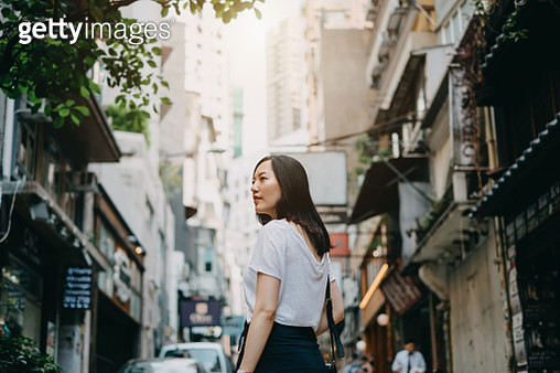 Beautiful young woman walking down streets of Hong Kong - gettyimageskorea