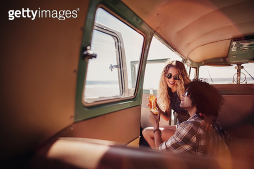 Young Hipster Couple Smiling and Toasting Beer in Retro Van - gettyimageskorea
