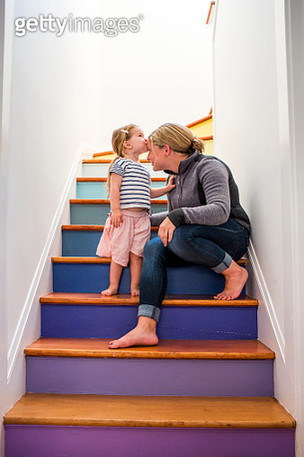 Caucasian girl kissing mother on forehead on multicolor staircase - gettyimageskorea