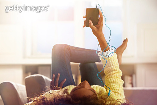 Woman relaxing at home listening to her phone. - gettyimageskorea