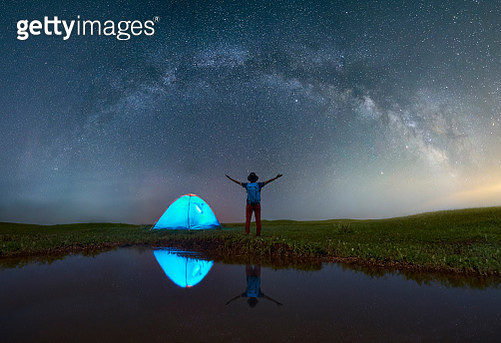 Rear View Of Mature Man With Arms Outstretched Standing On Grassy Field By Lake At Campsite Against Star Field - gettyimageskorea