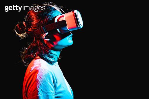 Woman using Virtual Reality headset at night - gettyimageskorea