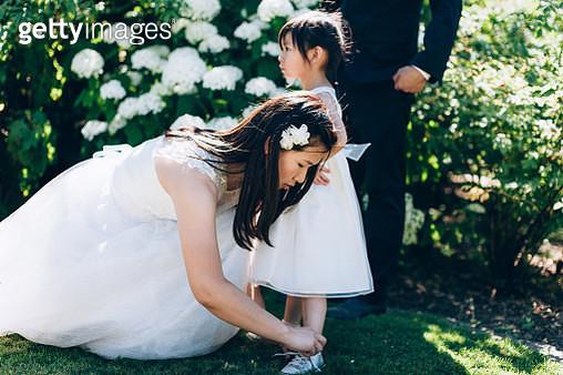 Bride kneeling and tying daughters shoelace - gettyimageskorea