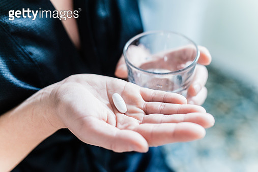 Woman hand and pill and glass of water. - gettyimageskorea