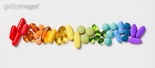 Pills arranged in a spectrum of colours. - gettyimageskorea