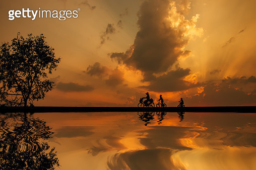 Silhouette people driving bicycles. - gettyimageskorea