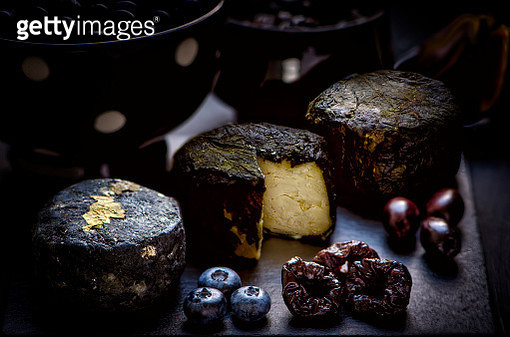 Three goat cheeses chevre in various coating: (charcoal or ash, nettle leaves, grape leaves) with blueberries, prunes, olives and figs, served on the black slate board - gettyimageskorea