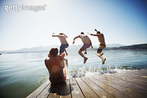 Woman sitting on the edge of floating dock while three men jump into water - gettyimageskorea