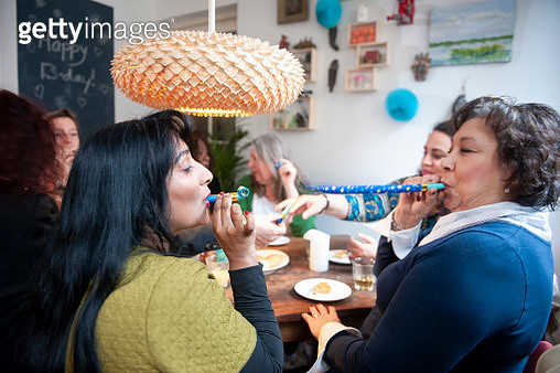 Mixed group of women celebrating friend's birthday with a party, playing with party horns - gettyimageskorea