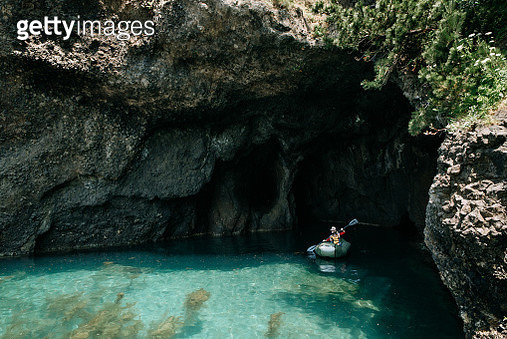Mother and child paddling packraft boat in sea cave, Japan - gettyimageskorea