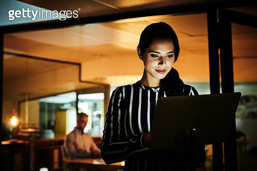 Shot of a young businesswoman using a laptop in an office at night - gettyimageskorea