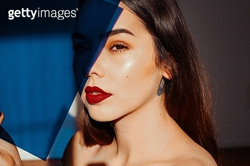 Close-Up Portrait Of Young Woman Holding Blue Paper At Home - gettyimageskorea
