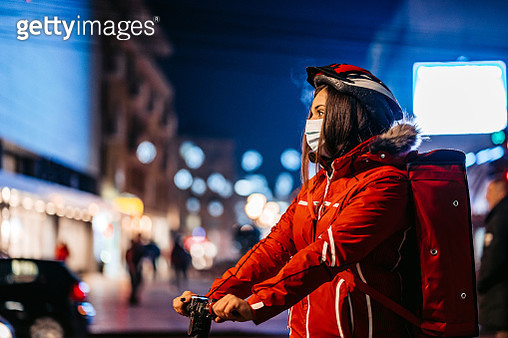 Delivery woman driving electric scooter - gettyimageskorea