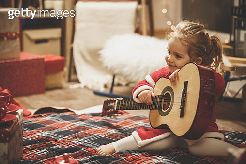 Full length shot of adorable little two year old girl sitting on a living room floor in her cozy winter pajama and holding a guitar while smiling and looking away. - gettyimageskorea