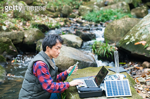An environmental researcher monitoring water quality from a solar powered field laboratory - gettyimageskorea