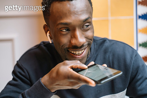 Portrait of smiling young man with wireless earphones on the phone - gettyimageskorea