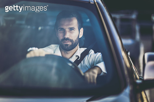 Young businessman going to work by car and thinking of something. - gettyimageskorea