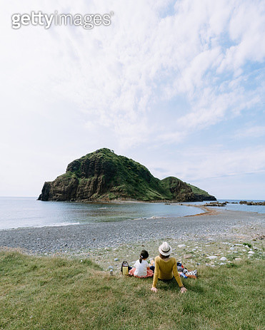Mother and child relaxing by coast, Sadoshima Island, Niigata, Japan - gettyimageskorea