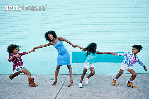 Girls pulling arms of woman in opposite directions - gettyimageskorea