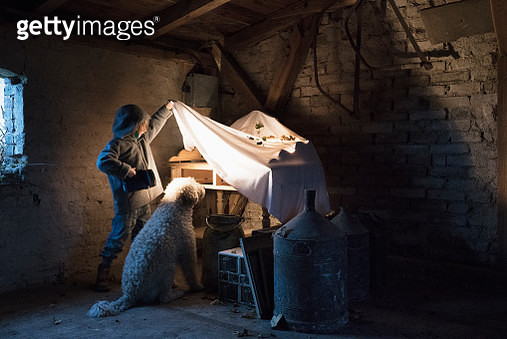 Girl and dog with flashlight peeking under cloth in carpentry workshop - gettyimageskorea