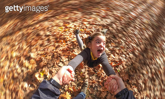 Smiling girl spinning and holding dad's hands - gettyimageskorea