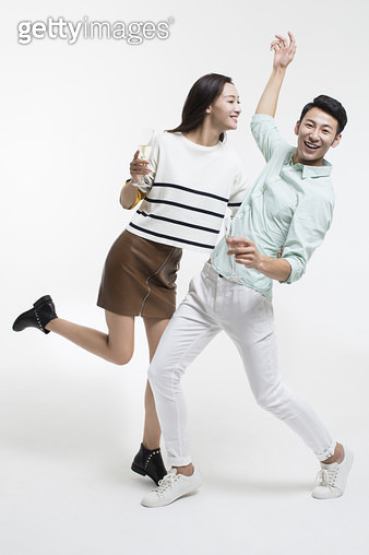 Cheerful young Chinese couple drinking champagne - gettyimageskorea