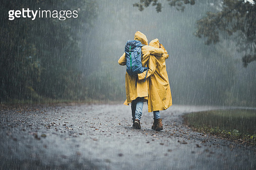 Rear view of loving couple in yellow raincoats hiking through park on a rainy day. Copy space. - gettyimageskorea