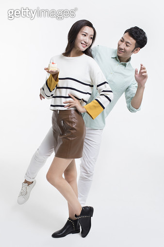 Cheerful young Chinese couple with a piece of cake - gettyimageskorea