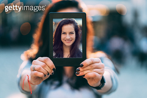 Smiling woman showing photo on tablet - gettyimageskorea