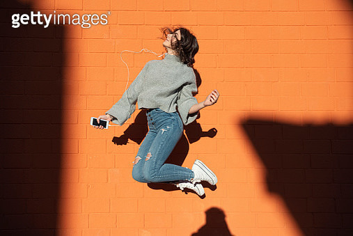 Young Woman listening to the music and jumping - gettyimageskorea
