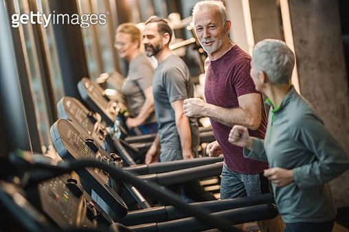 Group of happy active seniors talking while jogging on treadmills in a gym. - gettyimageskorea