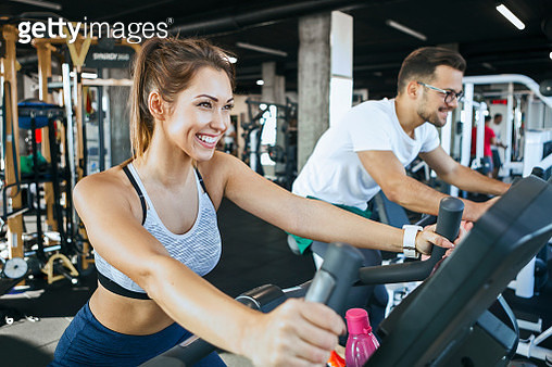 Happy young woman cycling at the gym - gettyimageskorea
