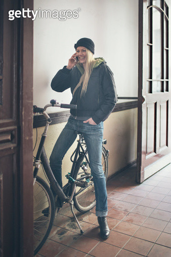 Woman with her bicycle on a porch talking with the mobile phone. - gettyimageskorea